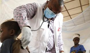 Theophile, MSF emergency team doctor, examines a child with measles at the Bosobolo general referral hospital, February 2021. © Franck Ngonga/MSF