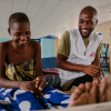 Esther, an advanced HIV patient interacting with Moses Luhanga, MSF Information Education and Communication Manager. In the picture, Moses is finding out how Esther is feeling. © Isabel Corthier/MSF